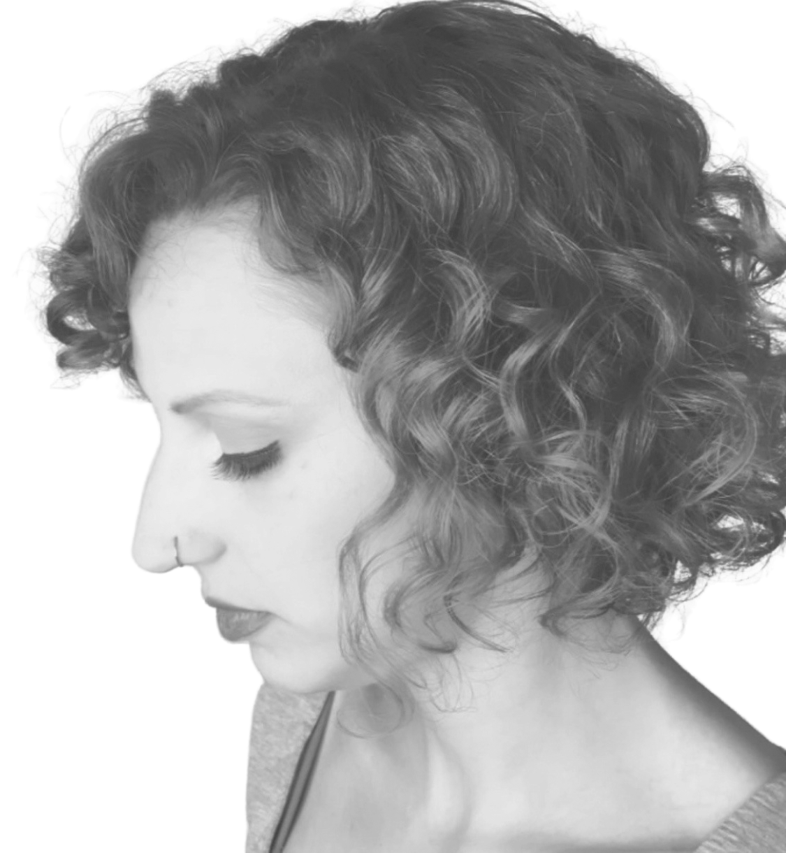 Side view of woman looking left showing her short curly hair