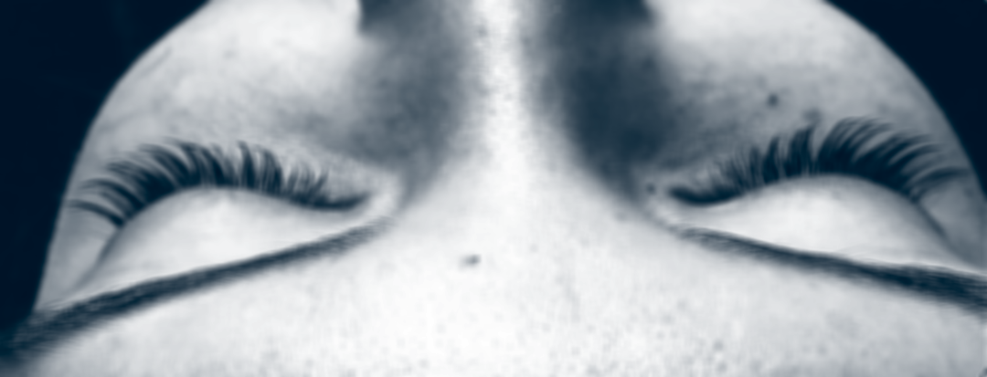 black and white close up view of woman's closed eyes